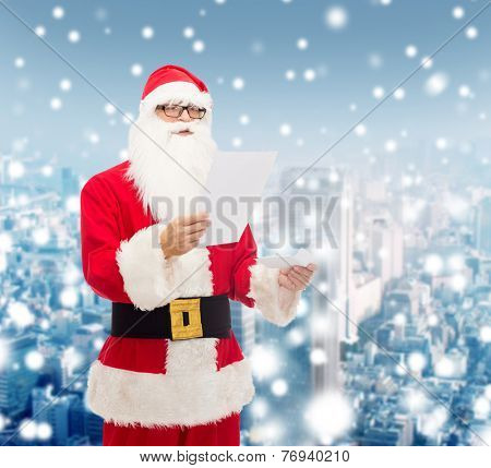 christmas, holidays and people concept - man in costume of santa claus reading letter over snowy city background