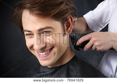 Hairdresser cuts hair young boy