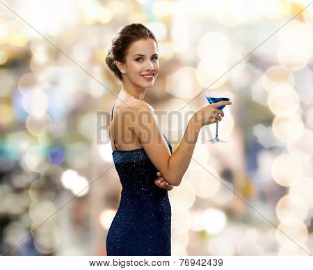party, drinks, holidays, luxury and celebration concept - smiling woman in evening dress holding cocktail over lights background