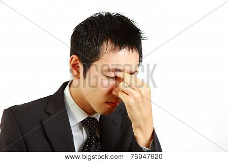 Japanese businessman suffer from a eyestrain