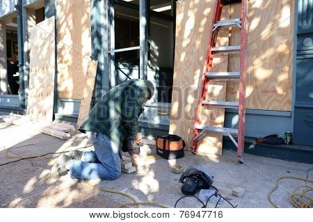 FERGUSON, MO/USA - NOVEMBER 25, 2014: Man works to board up windows in Ferguson as business in the aftermath of riots.