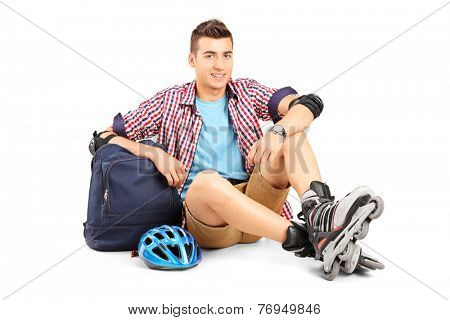 Young man with rollerblades sitting on the floor isolated on white background