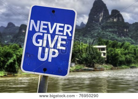 Never Give Up sign with a rural background