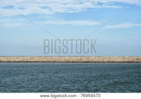 Stone Pier Dividing Cloudy Sky And Wavy Sea