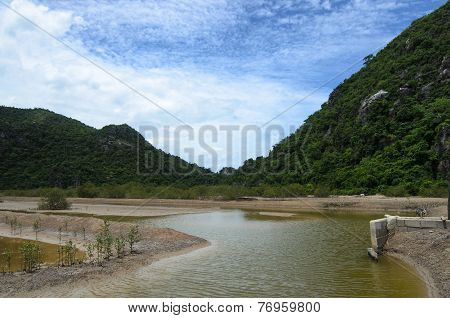 Small Pond In A Marshland With Stunning Rocks At The Background Under Awesome Cloudy Sky