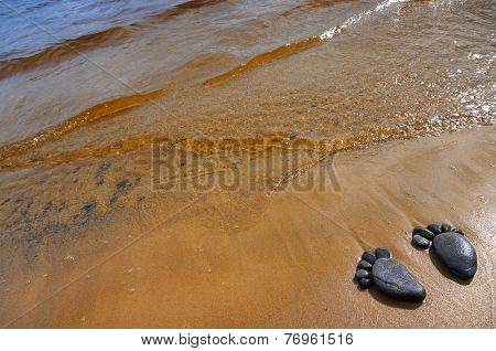 pair trace feet made of a pebble stone on the sea sandy coast, surface texture top view background