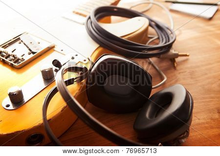Guitar recording scene. An electric guitar, memo pad , and a professional grade headphones on a rustic or bare wooden table, with by-the-window type warm light.