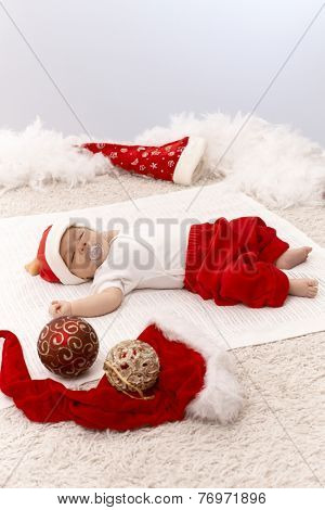 Newborn baby sleeping in Santa hat among christmas ornaments.