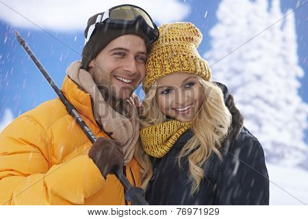 Happy skiing couple hugging, smiling at wintertime.