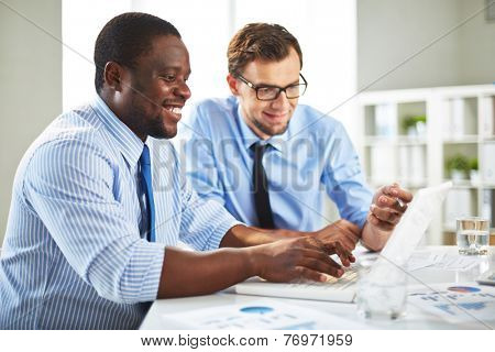 Two colleagues discussing data on laptop