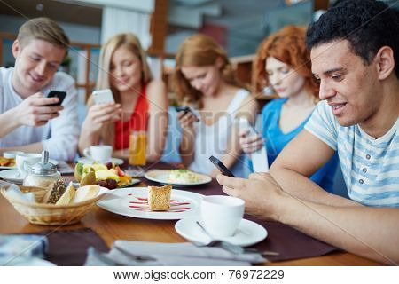 Friends sitting at caf���© absorbed in their phones