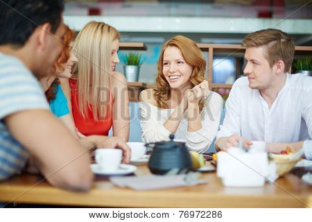 Young woman sitting at caf�?�?�?�© among her friends