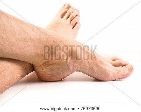 Hairy Legs And Feet Of Male Person Resting Towards White Background