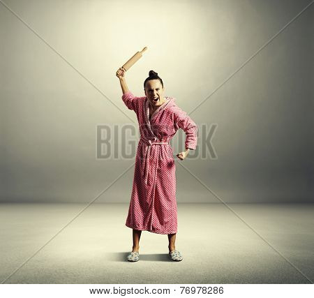 angry screaming housewife holding rolling pin and looking at camera over dark background