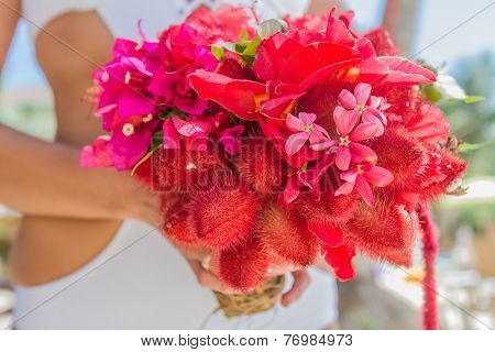 wedding bouquet from local tropical flowers in bride's hands on natural background