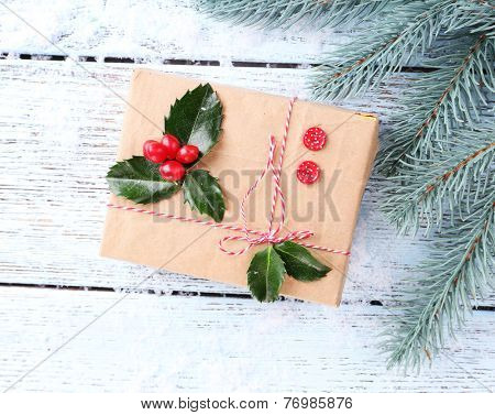 Beautiful Cristmas gift with European Holly (Ilex aquifolium) on wooden background