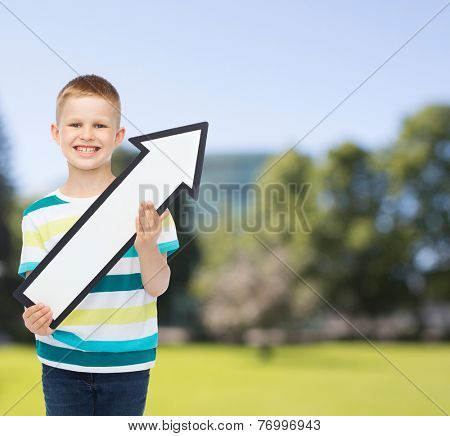 advertising, direction, nature and childhood concept - smiling little boy with white blank arrow pointing up over park background