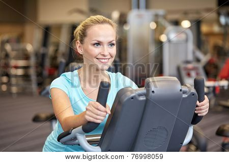 sport, fitness, lifestyle, technology and people concept - smiling woman exercising on exercise bike in gym