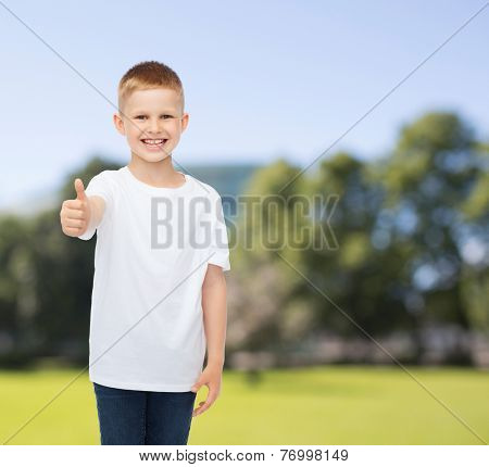 advertising, summer, people and childhood concept - smiling little boy in white blank t-shirt showing thumbs up over park background