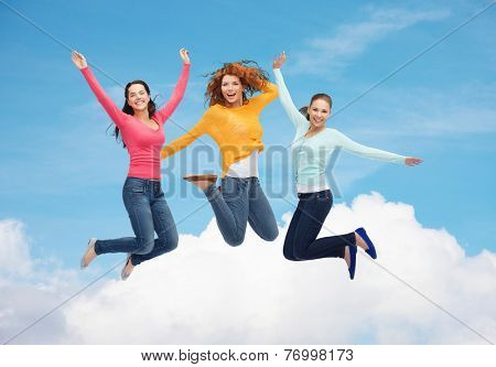 happiness, freedom, friendship, movement and people concept - group of smiling young women jumping in air over blue sky with white cloud background
