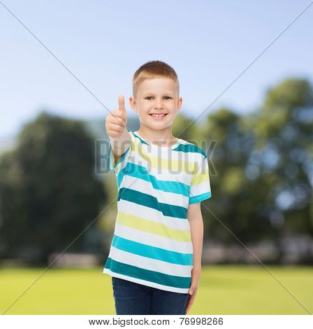 happiness, childhood, nature and people concept - smiling little boy in casual clothes showing thumbs up over green park background