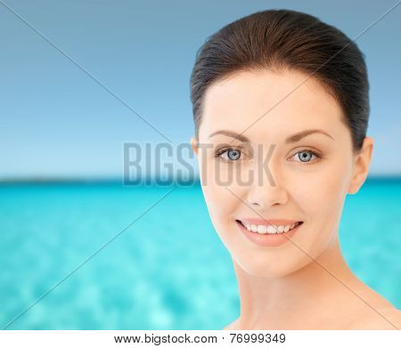 beauty, people and health concept - beautiful young woman face over blue water and sky background