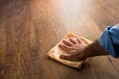 stock photo of cleaning house  - Male hand cleaning and rubbing hardwood floor with a microfiber cloth - JPG