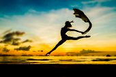 image of jumping  - silhouette of jumping girl on tropical sunset sea and sky background - JPG