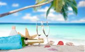 stock photo of flute  - Champagne flutes on sunny beach - JPG
