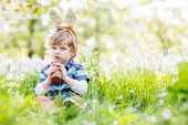 stock photo of bunny costume  - Funny child wearing Easter bunny ears at spring green grass and blooming apple garden eating chocolate bunny and having fun outdoors - JPG
