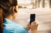 picture of hispanic  - Mid adult hispanic person with mobile phone and bluetooth headset typing on telephone in the street - JPG