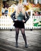 stock photo of nylons  - Portrait of a confident blond teenager with long hair wearing a leather jacket green glittery t - JPG