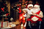 stock photo of letters to santa claus  - Little boy and Santa Claus reading letters from children - JPG