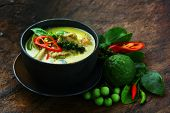 stock photo of curry chicken  - Thai traditional chicken green curry with old wooden background - JPG