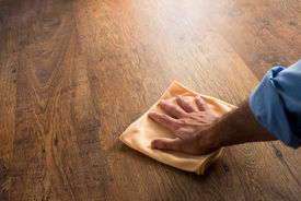 image of disinfection  - Male hand cleaning and rubbing hardwood floor with a microfiber cloth - JPG