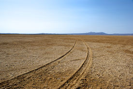 stock photo of flat-bed  - Tire tracks lead into the distance in a flat dry lake bed in the Mojave desert of southern California - JPG