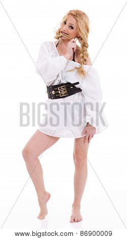 Barefoot woman in a long white shirt with black belt