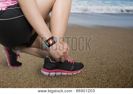 Sport Woman Tying Shoelaces Wearing Health Sensor Smartwatch With Beach