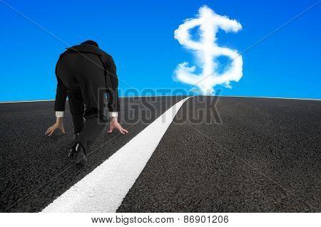 Businessman Ready To Run On Asphalt Road With Dollar Sign
