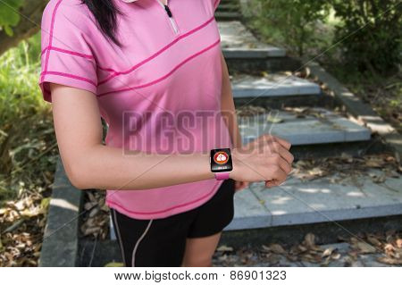 Sport Woman Wearing Smartwatch With Health Sensor On Forest Trail