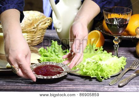 Female Hands Put Cowberry Sauce In A Bowl On A Table