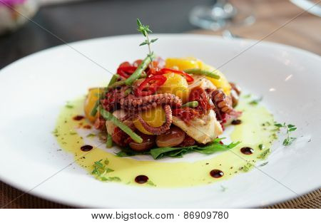 Appetizer with grilled octopus, potatoes and vegetables on plate