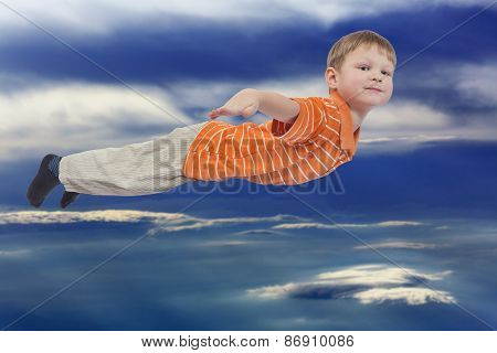 Young boy flying with cloud sky in background