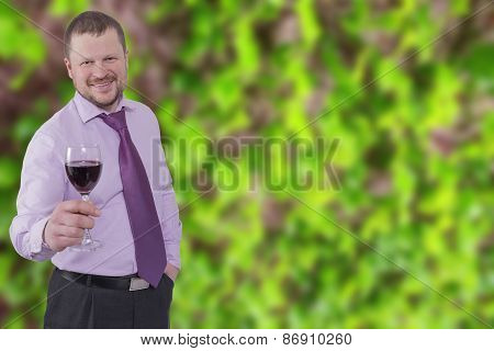 Businessman holding glass of wine with vineyard in background