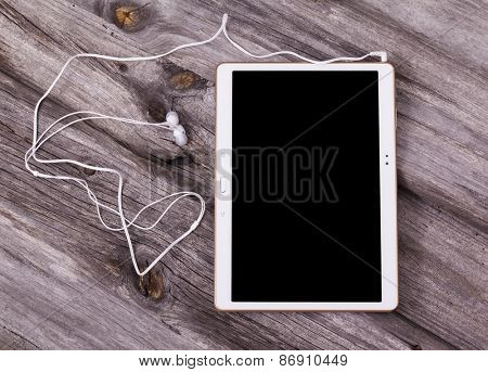 Digital tablet computer with earphones against wooden background