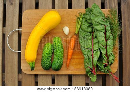 Fresh Vegetables: Yellow Marrow, Cucumbers, Carrot And Chard On Wooden Board