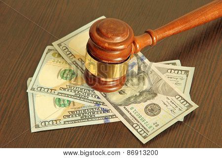 Judge Gavel And Dollar Banknotes On Wooden Table.
