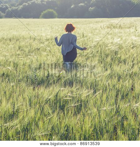 girl running across green field in the morning