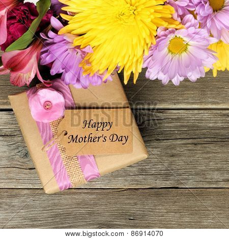 Mother's Day gift box with flowers on wood