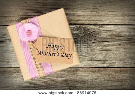 Gift box with Mother's Day tag on wood